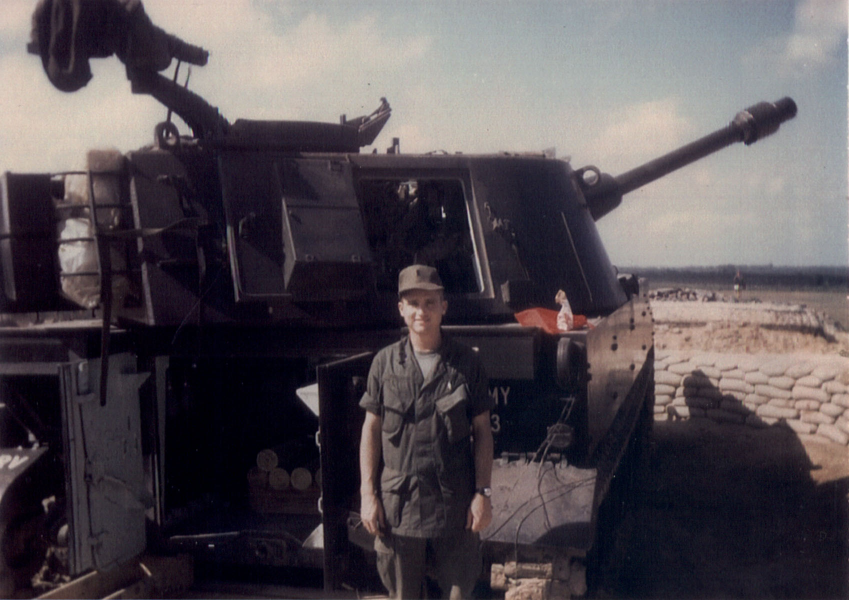 Patterson standing in front of a 105 self propelled Howitzer.
