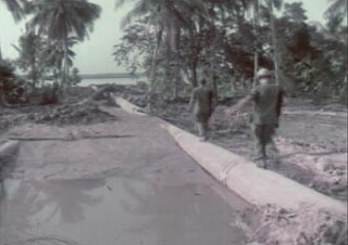 Screenshot from corrected film of two men walking on a pipe at the Dong Tam Base Camp Construction.