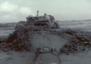 Screenshot from the corrected film of a pipe spraying water and a bulldozer moving dirt during the construction of the camp.