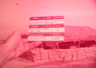 Screenshot from original film, William Foulke's clacker with his name on it. Film is red tinted.