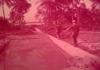 Screenshot from original film of two men walking on a pipe at the Dong Tam Base Camp Construction. Image is red tinted.