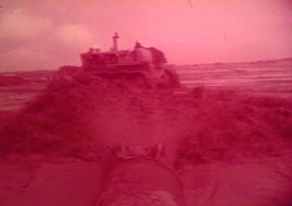 Screenshot from the original film of a pipe spraying water and a bulldozer moving dirt during the construction of the camp. Image is red tinted.
