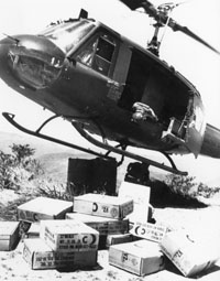 A UH-1D helicopter makes an aerial delivery of supplies:  C-rations.: U.S. Army Aviation Museum Volunteer Archivists Collection [VA058991]