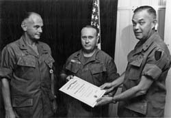 Officers Call- Room 113, Building 5002, 0900 hours, 6 Dec 69. Brigadier General H. H. Cooksey presents the Meritorious Unit Commendation Medal to Colonel John E. Reid and Sergeant Major John H. Cupp, Army Concept Team in Vietnam, APO 96384.: Richard L. Clarkson Collection [VA060939]