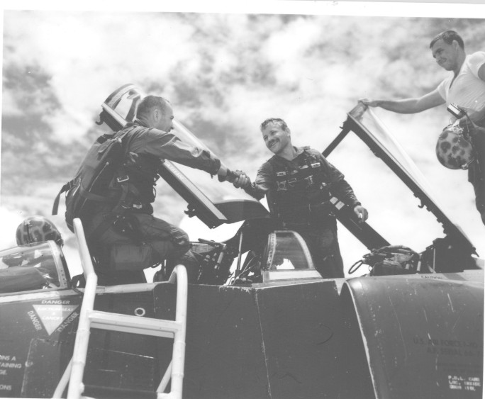 First Air Force F-4 Navigator Completes 100 Missions Over North - Southeast Asia - Major Ronald C. Herrick (left), congratulates his back-seater, Captain Herbert Altman (center) upon completion of his 300th combat mission over the Southern Panhandle of North Vietnam. Altman was the first F-4 Navigator to have completed 100 combat missions over North Vietnam.