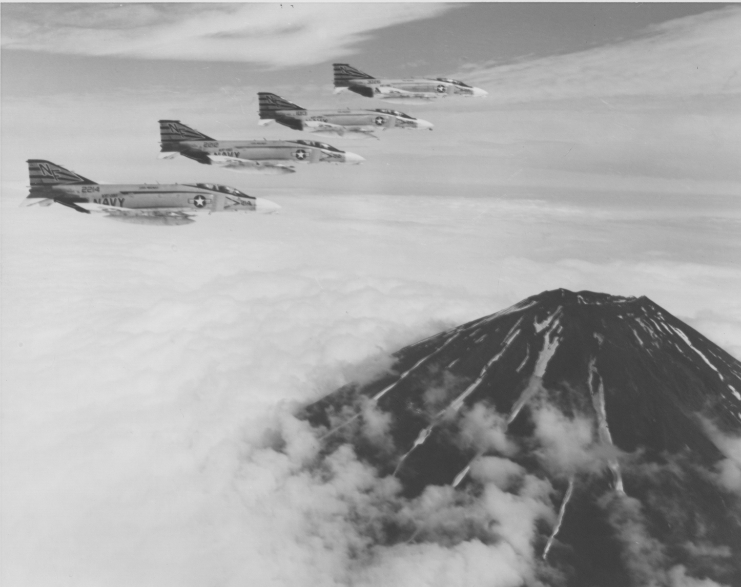 Four Navy F-4 Phantoms over a volcano.