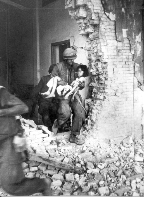 A US Marine carries a seriously wounded Vietnamese child from the ruins of a home in Hue. The provincial capital city was the target of violent VC attacks following the start of the Tet (Lunar new year).