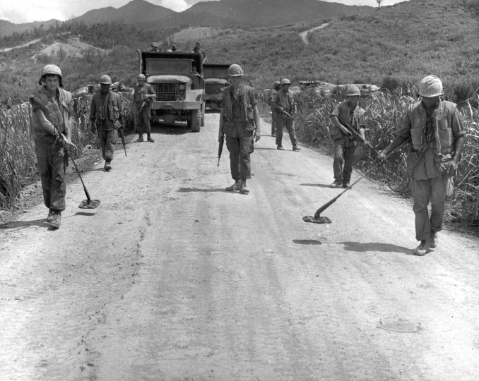 "Mine Sweep-- A Marine mine sweep team of ""A"" Company, 3rd Engineer Battalion, checks a road west of Ca Lu for enemy Mines or dud rounds. This sweep, like many others in the Northern I Corps, is conducted each morning before traffic is permitted to use the road."