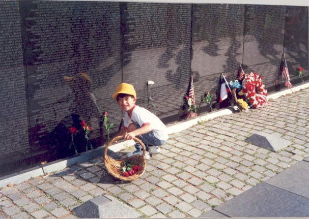 Young boy leaving roses at the Vietnam Memorial
